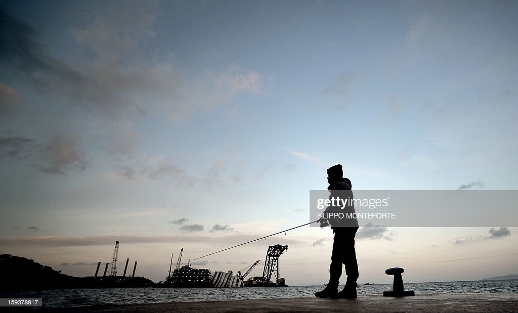 A man fishes in the port of the Italian island of Giglio on January 12, 2013, where the Costa Concordia cruise ship (background) wreck will be removed from the island of Giglio by September at the latest, the head of Italy's civil protection agency said today, the eve of the first anniversary of the disaster which claimed 32 lives. AFP PHOTO / FILIPPO MONTEFORTE
