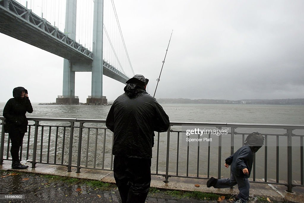 A man fishes near the Verrazano Bridge as Hurricane Sandy begins to affect the area on October 29, 2012 in the in Brooklyn borough of New York City. The storm, which threatens 50 million people in the eastern third of the U.S., is expected to bring days of rain, high winds and possibly heavy snow. New York Governor Andrew Cuomo announced the closure of all New York City bus, subway and commuter rail service as of Sunday evening.