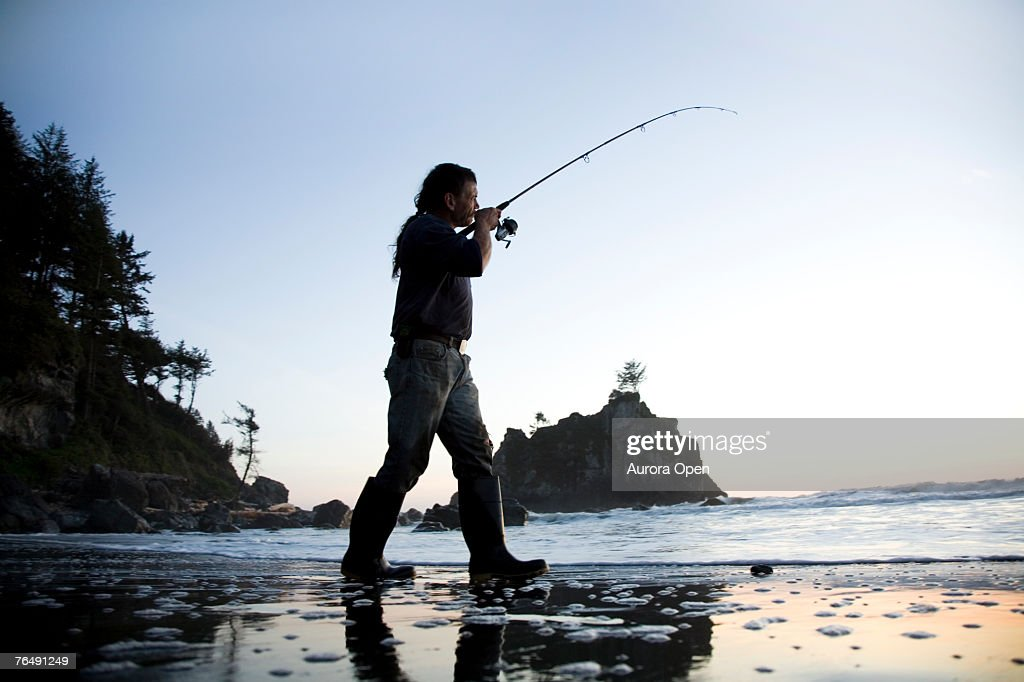 A man fishes off the coast of California near Redwood National Park. : Stock Photo
