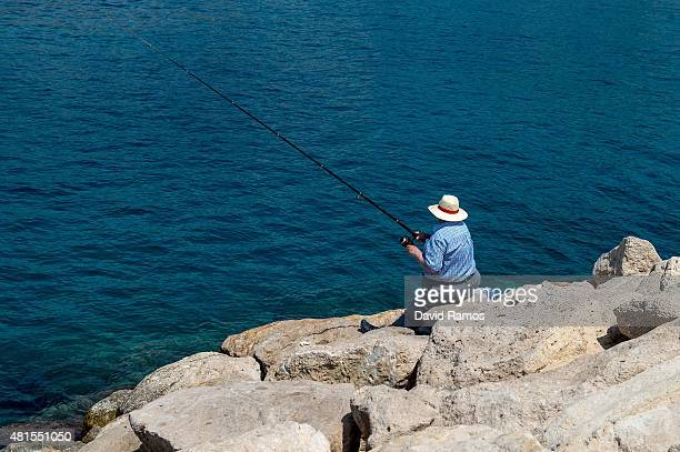 A man fishes on a pier at Poniente Beach on July 22 2015 in Benidorm Spain Spain has set a new record for visitors with 292 million visitors in June...