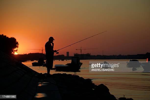 A man fishes on the banks of the Danube river in Zemun near Belgrade on July 26 2013 Along its 588 km course through Serbia it passes through the...