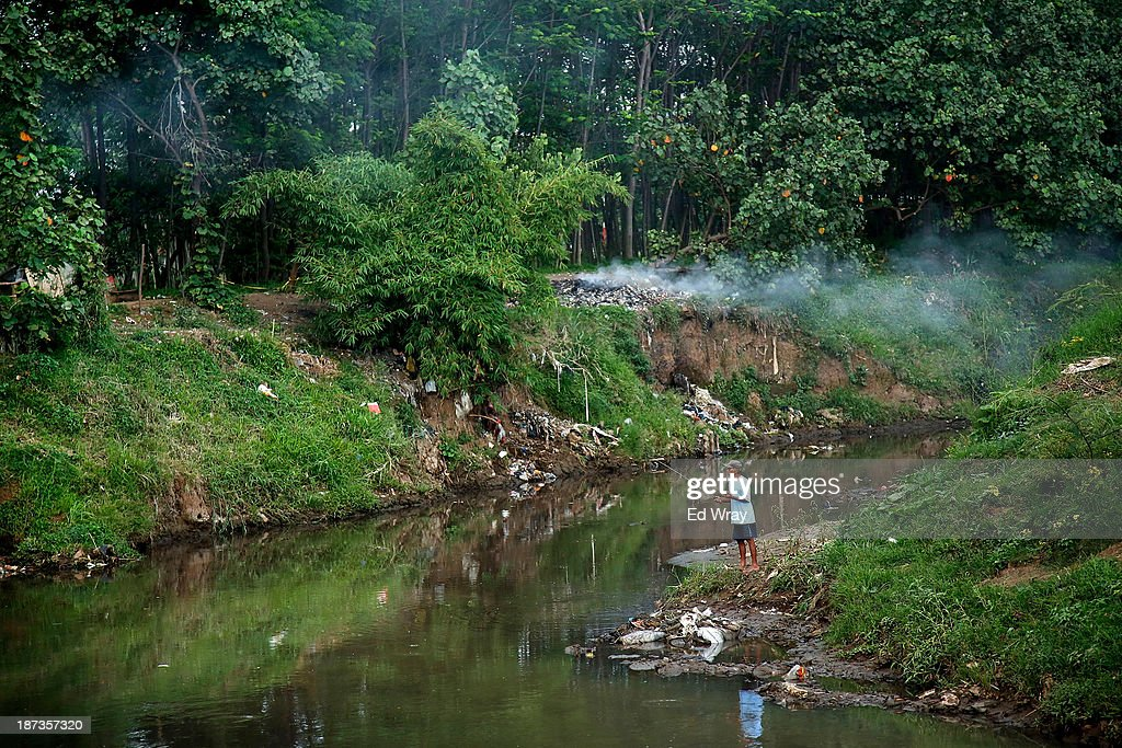 A man fishes on the banks of the heavily polluted Citarum river near the town of Majalaya, a major textile producer on November 7, 2013 in Majalaya, Indonesia. The effects of domestic and industrial waste from factories along the river have prompted two leading environmental groups, Green Cross of Switzerland and the Blacksmith Institute, to name the Citarum river as one of the earth's 10 most polluted places in their annual report.