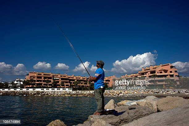 A man fishes on the seaside on October 15 2010 in front of a luxury apartment complex in Marbella which was built on the land where was the villa...