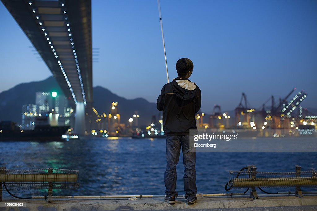A man fishes opposite the Kwai Tsing Container Terminals with Stonecutters Bridge overhead in Hong Kong, China, on Monday, Jan. 21, 2013. Hong Kong is scheduled to release export figures for December on Jan. 24. Photographer: Jerome Favre/Bloomberg via Getty Images