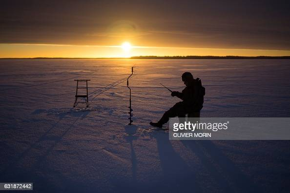 TOPSHOT A man fishes through the ice on January 17 2017 at sunrise on the frozen sea in Vaasa by 15°C / AFP / OLIVIER MORIN