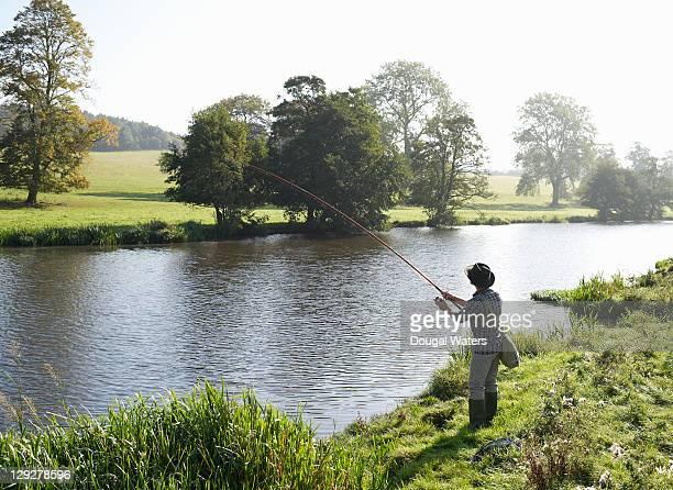 Man fishing at edge of lake.