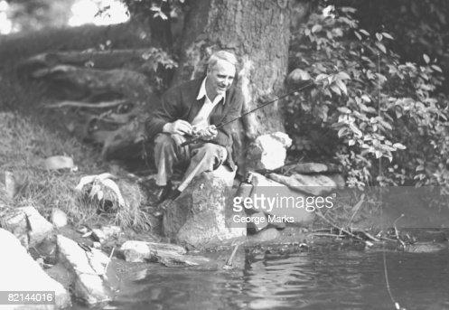 Man fishing at river bank, (B&W) : Stock Photo