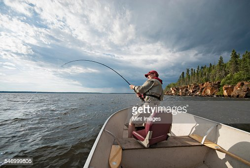 A man fishing from an open boat offshore. A fish on the line. The fishing rod bending from the weight.