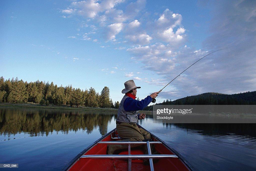 Man fishing from canoe on lake : Stock Photo