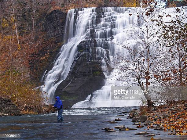 Man fishing in front of Waterfall