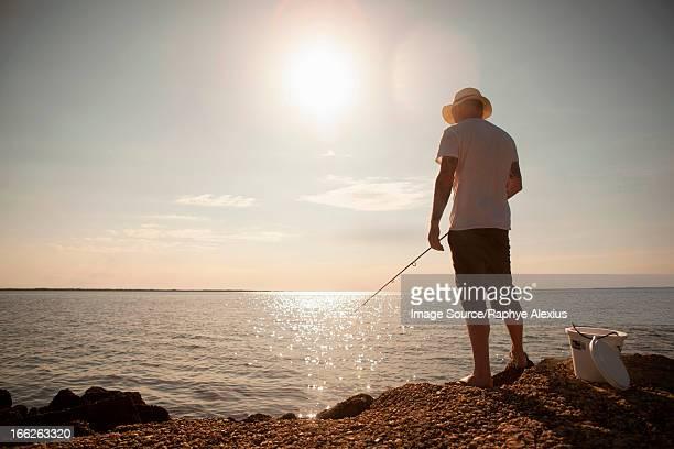 Man fishing in still ocean
