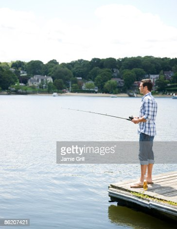 Man fishing off dock with beer at feet stock photo getty for Fishing off a pier