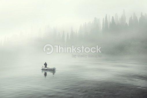 Man fishing on a boat in a mistic foggy lake : Foto de stock