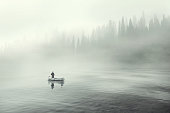 Man fishing on a boat in a mistic foggy lake