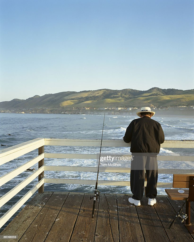 Man fishing on pier stock photo getty images for Fishing without a license california