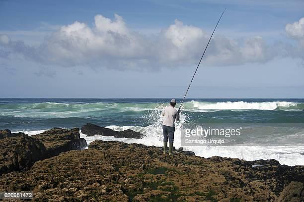 Man fishing on rocky coastline
