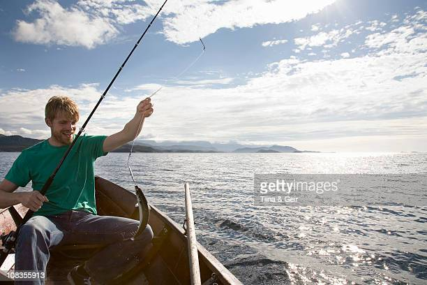 Man fishing on wooden boat