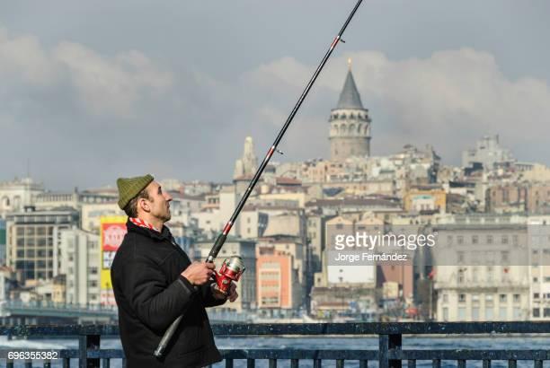 Man fishing with a fish line at Galata bridge