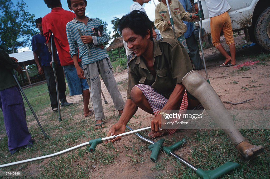 """A man fits pads to the new crutches he received from Veterans International Cambodia on a trip to Veal Thom as his son looks on. Deep in the hinterlands, down a rutted dirt road, a small village shelters the remnants of Cambodia's civil war. Some 200 disabled veterans - both Khmer Rouge and government soldiers - and their families have moved to Veal Thom, or """"Big Field."""" There they build huts, grow rice, cultivate flowers and do what society will not allow in their homelands: live in peace. Though they lost limbs and parts of their lives in Cambodia's civil war, their wounds mark them as outcasts in the Cambodian society.."""
