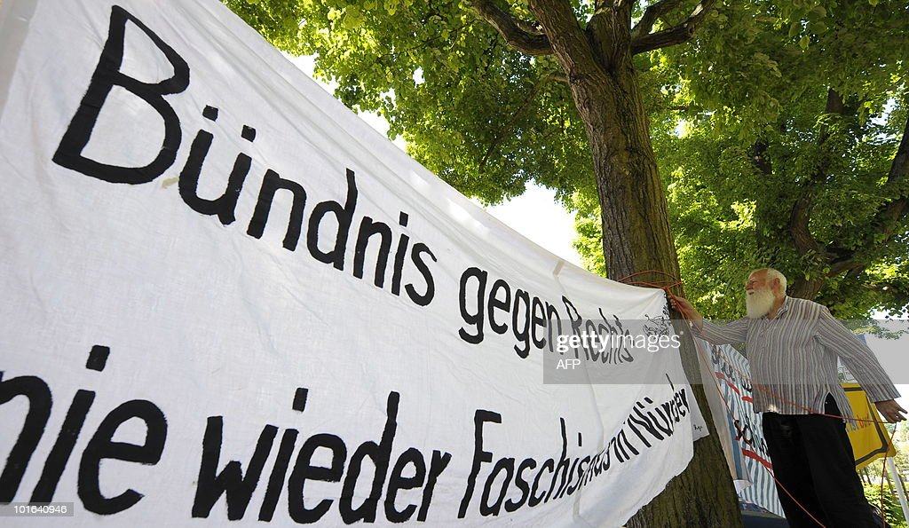 A man fixes a banner reading 'alliance against right - never again fascism' during a demonstration against the party congress of the German right-wing extremist party NPD (Nationale Partei Deutschland) in Bamberg, southern Germany, June 5, 2010. Thousands of demonstrators staged a peaceful protest against the party, among others by building a human chain.