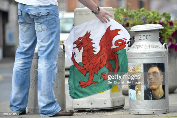 A man fixes a Welsh flag between two milk churns that are acting as containers for donations to help the troops at a memorial to Richard Hunt the...