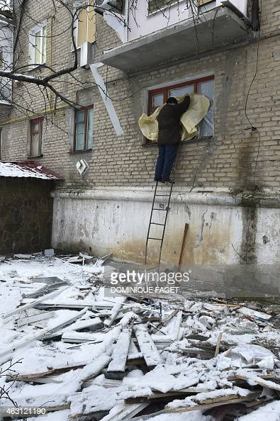 A man fixes a window damaged by shelling on febuary 10 for 10 x 40 window