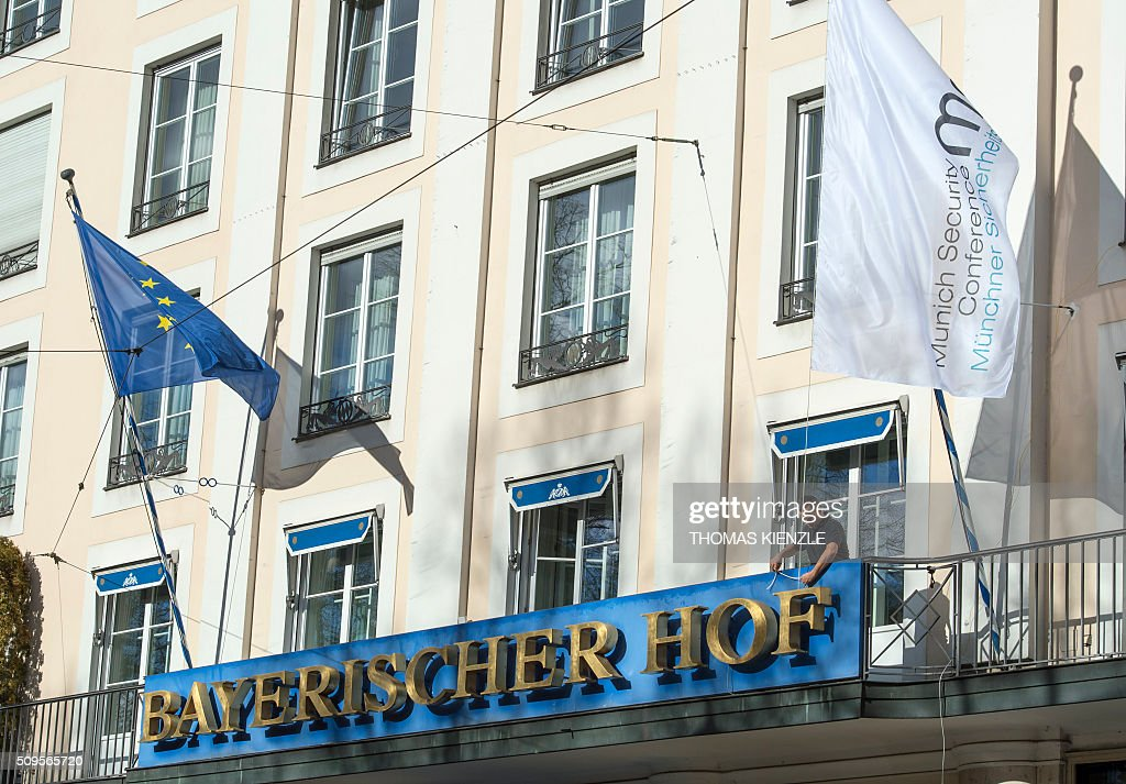 A man fixes the flag of the 52nd Munich Security Conference (MSC) on a balcony of the Bayerischer Hof hotel in Munich, southern Germany, on February 11, 2016. The Munich Security Conference takes place from February 12 und until February 14, 2016. / AFP / THOMAS KIENZLE