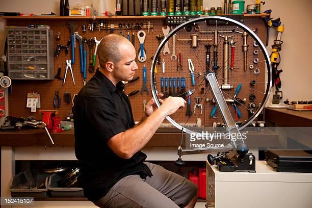Man fixing bicycle rim in workshop