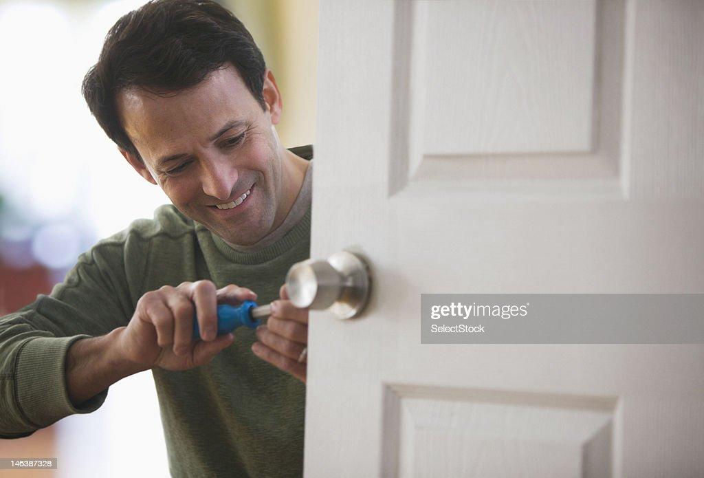 Man fixing door nob : Stock Photo