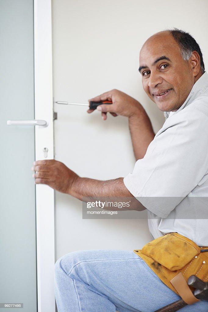 Man fixing door : Stock Photo