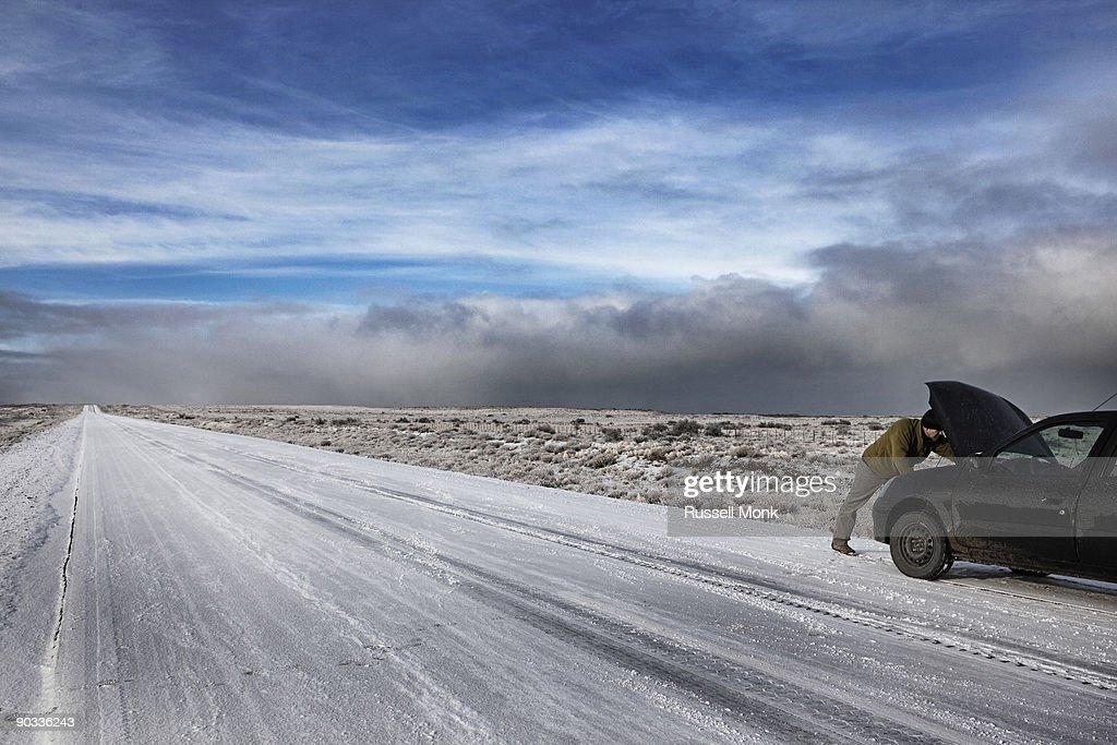 Man fixing his car on remote winter road : Stock Photo