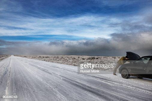 Man fixing his car on remote winter road : Stockfoto