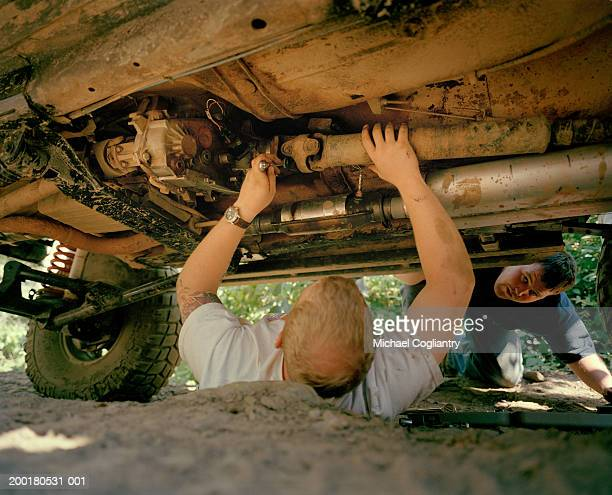 Man fixing off road vehicle, ground view