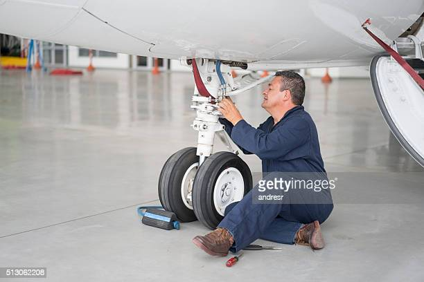 Man fixing the landing gear of a plane