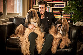 Man flanked by dogs on sofa