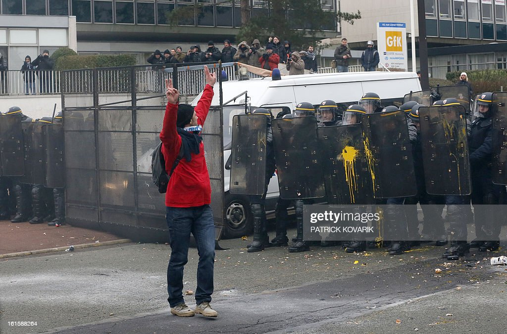 A man flashes the V-sign as she stands in front of anti-riot police as US Goodyear Tire & Rubber workers demonstrate in front of the group's headquarters in France, in Rueil-Malmaison, a Paris suburb, on February 12, 2013, at the time of an extraordinary central works council on the plan to shut down Goodyear's plant in Amiens, northern France. 'Closing the factory is the only option after five years of unsuccessful negotiations,' said a French-language statement issued on January 31, 2013 by Goodyear Dunlop Tires France, which employs about 3,200 people in the country across four sites.