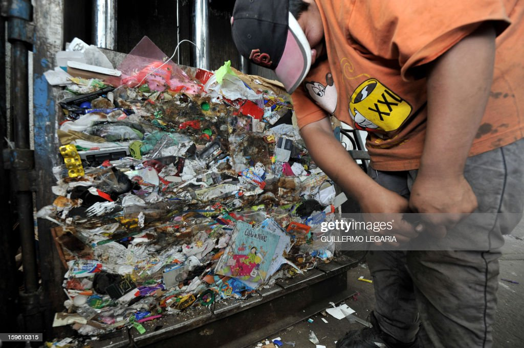 A man flattens recyclable garbage in an hydraulic press at La Alqueria Recycling Center in Bogota, Colombia, on January 17, 2013. Some 60 recyclers classify 10 tons daily of potentially recyclable waste at this recycling center wich is part of Bogota's Mayor program 'Basura Cero' (Zero waste). AFP PHOTO/Guillermo LEGARIA