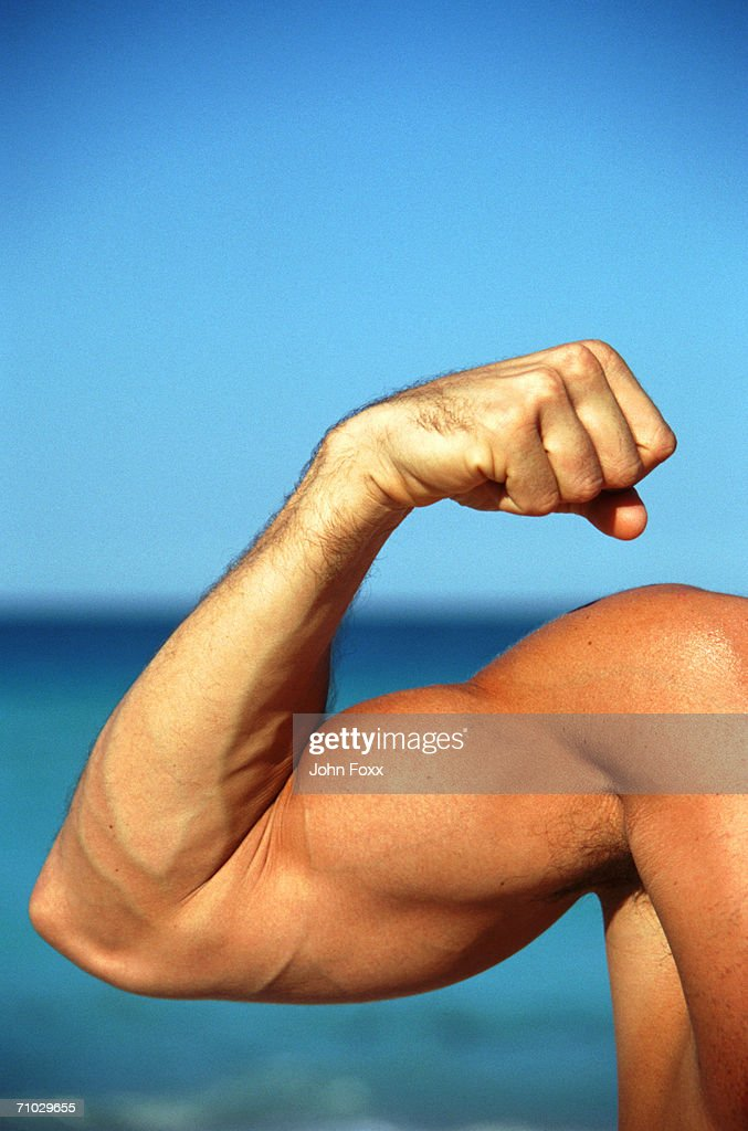 Man flexing muscles, focus on hand : Stock Photo