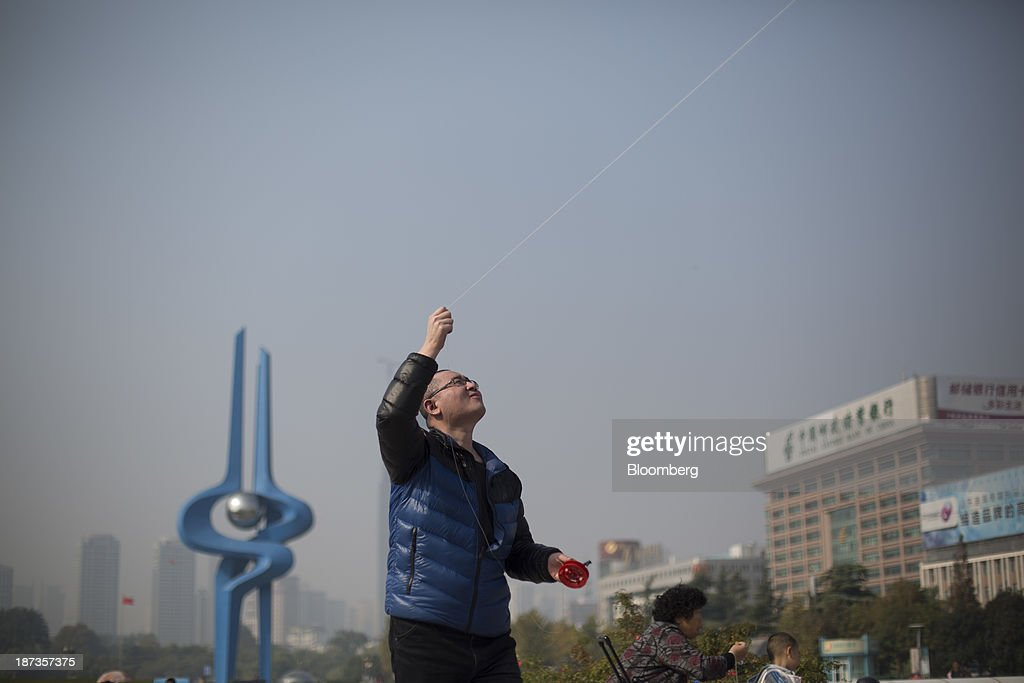 A man flies a kite at Spring City Square in Jinan, China, on Wednesday, Nov. 6, 2013. The third plenary session of the 18th Communist Party of China Central Committee will be held from Nov. 9 to Nov. 12 in Beijing. Photographer: Brent Lewin/Bloomberg via Getty Images