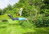 Man flies with wheelbarrow in a bush.