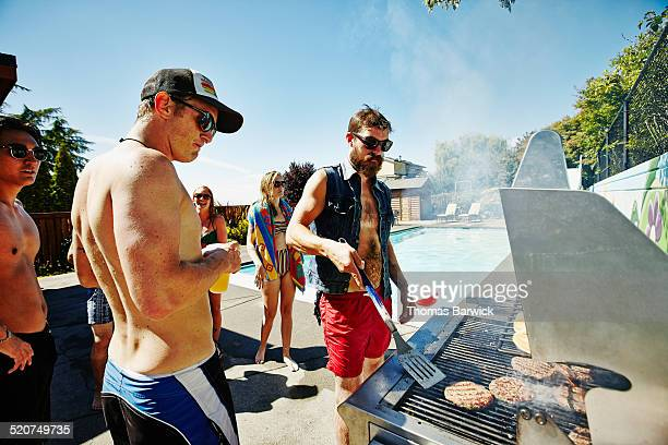 Man flipping burgers on barbecue during party