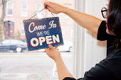 Man flipping over open sign in cafe