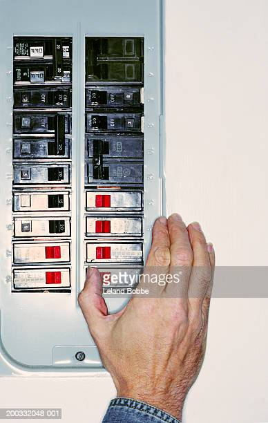 Man flipping switch on circuit breaker, close-up