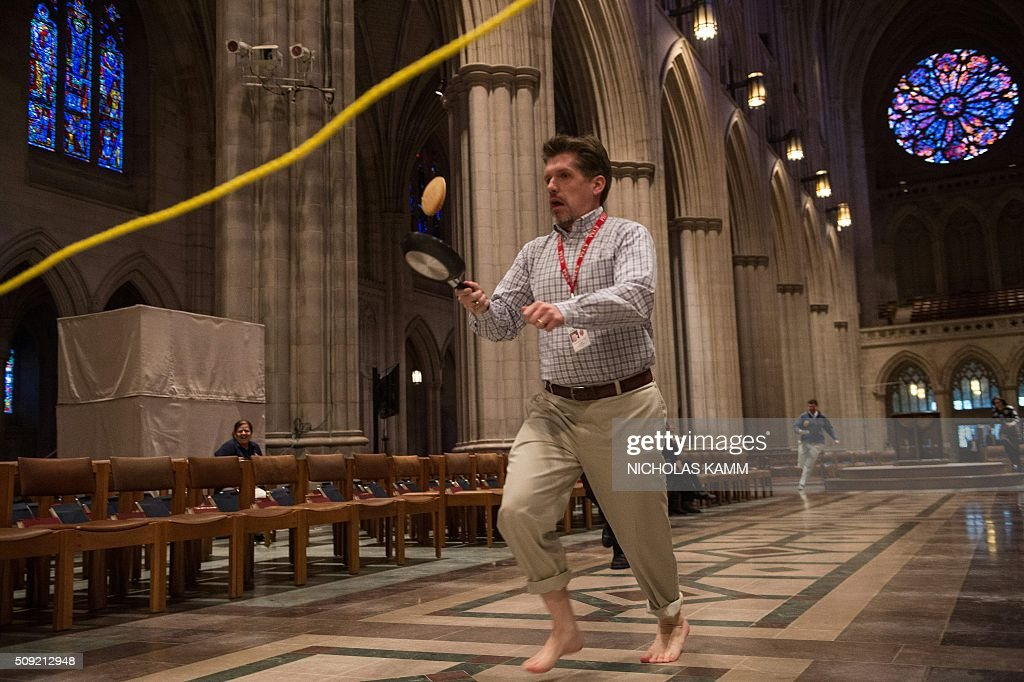 A man flips a pancake during the Shrove Tuesday Pancake Race at the National Cathedral in Washington, DC, on February 9, 2016. Shrove Tuesday, also known as Mardi Gras, precedes Ash Wednesday, the first day of Lent. / AFP / Nicholas Kamm