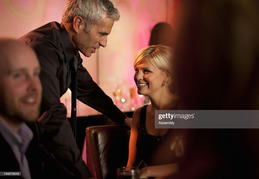 A man flirts with a woman at a bar. : Stock Photo