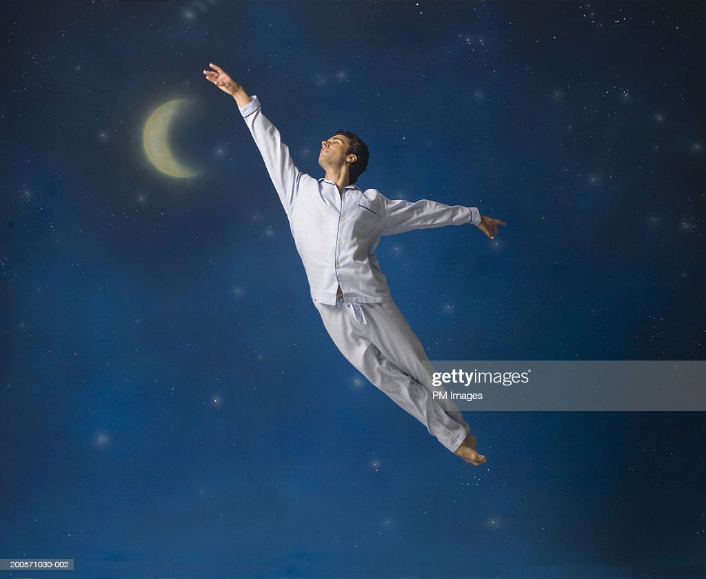 Man floating in mid-air with arms outstretched : Stock Photo