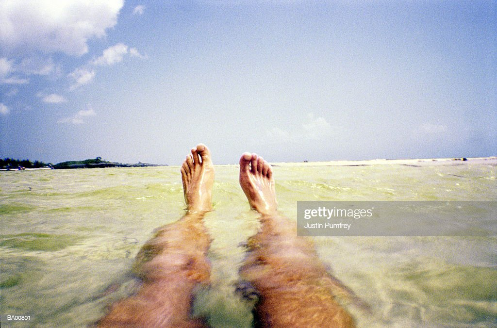 Man floating in sea, tropical island in background, low section : Stock Photo