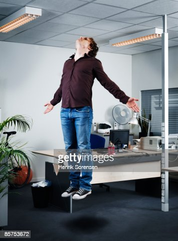 Man floating in the air in his offiice.