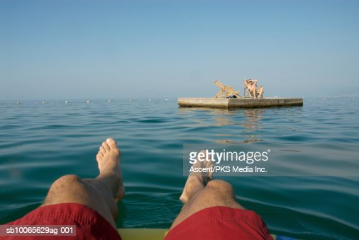 Man floating on water, woman sitting on chair in background