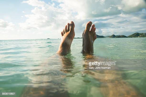 POV Man floats in tropical sea, feet out of water